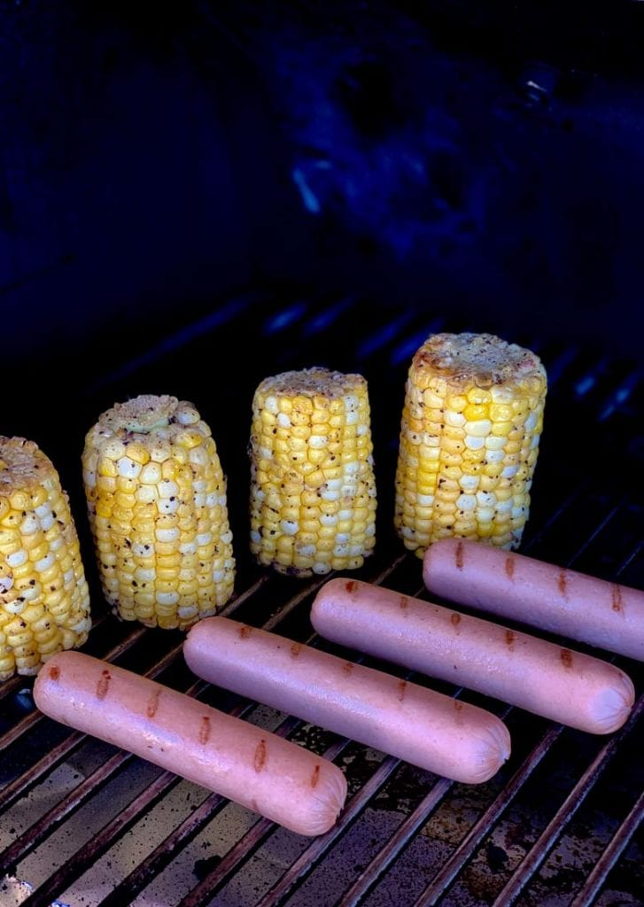 corn on the cob and hot dogs on the gill