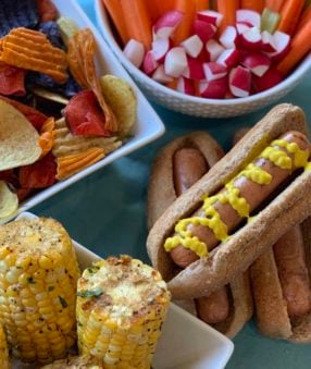 a bbq spread with corn, hot dogs, chips, and veggies