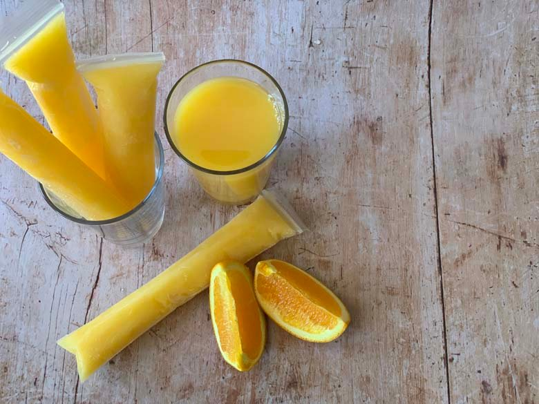 top down image of screwdriver popsicles, orange slices, and a glass of orange juice