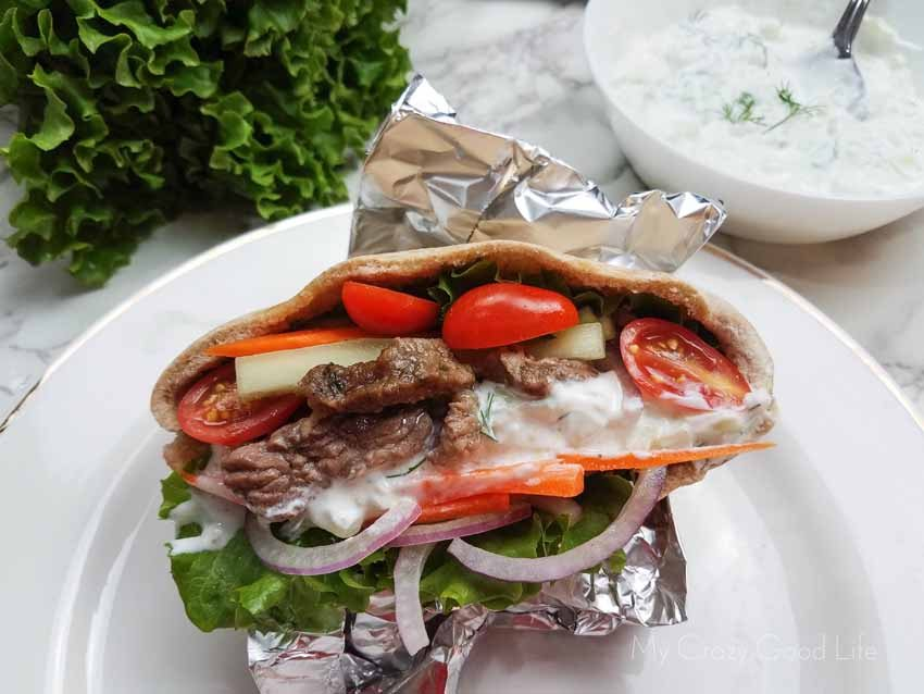 close up of beef gyros on a white plate