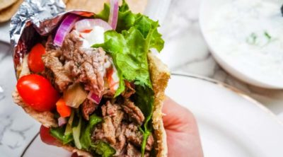 close up of hand holding steak gyro