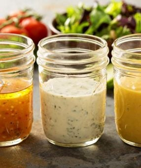 three mason jars with salad dressing
