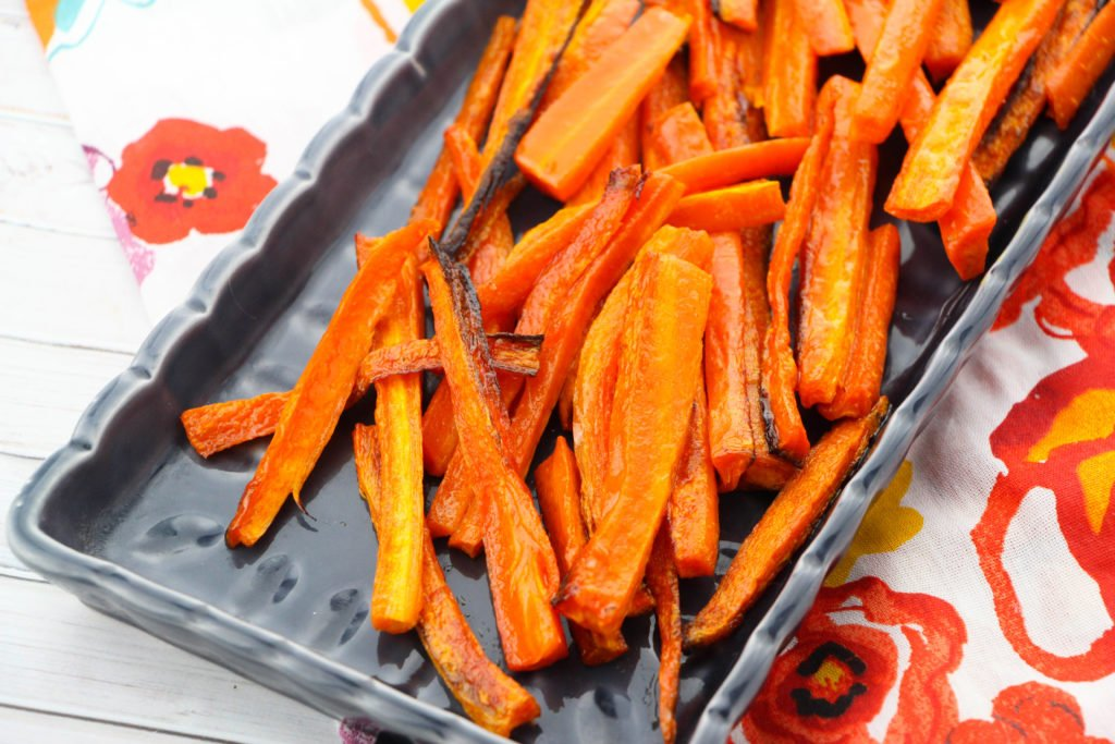 Carrot fries chopped and cooked in a black dish waiting to be eaten.