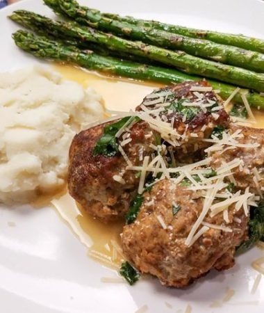 swedish meatballs on a white plate with asparagus and potatoes