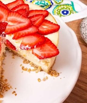 white plate with cheesecake, strawberries on top