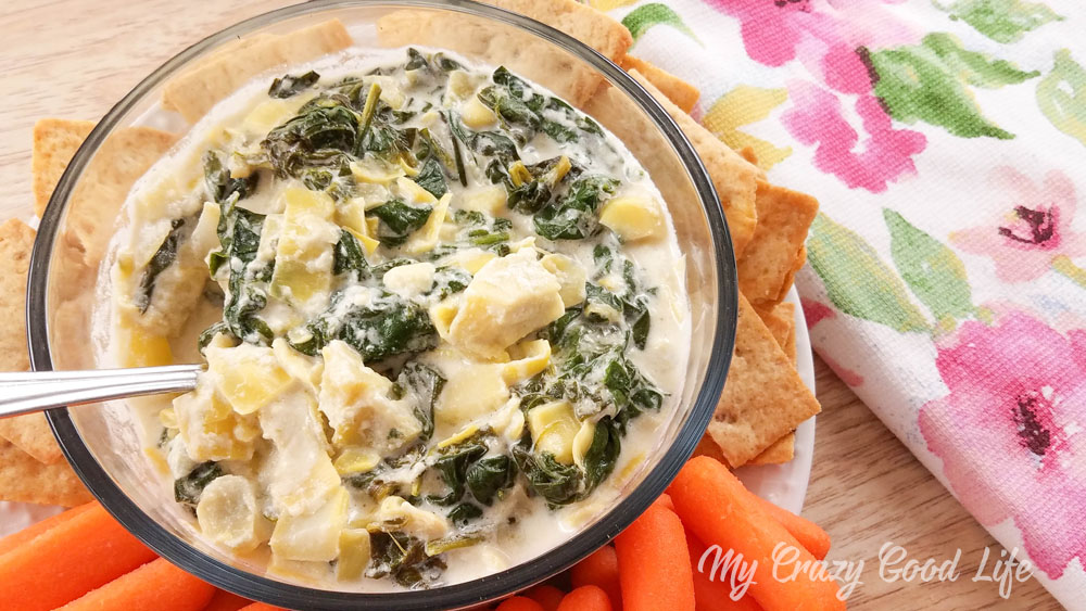 spinach and artichoke dip in a clear bowl with veggies