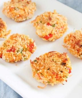 six crab cakes on a white platter