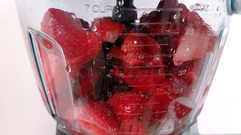 frozen strawberries, honey, and citrus juice in a blender