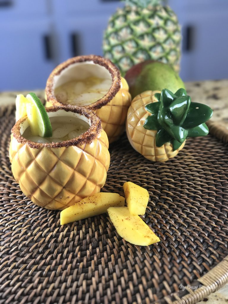 pineapple cups filled with margarita on a woven platter