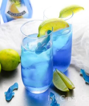 There's nothing better than curling up on the couch and enjoying Shark Week with a drink! This fun Shark Bite Margarita is the perfect Shark Week companion! Be careful... this one is strong, and it bites back! Shark Week Cocktails | Blue Margarita | Shark Week Margarita