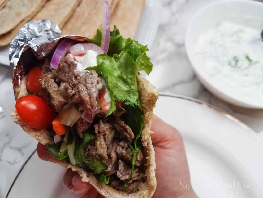Beef gyro in a hand being held up to show the open side which has meat, vegetables, and sauce inside.
