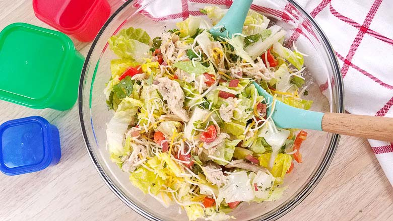 clear bowl with salad with crack chicken mixed in