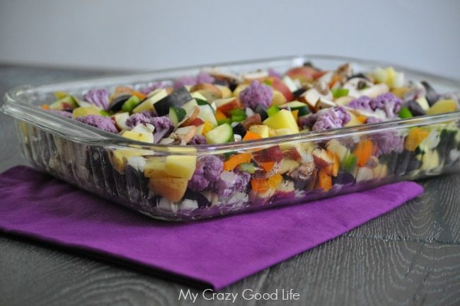 Casserole on a purple napkin on top of a wooden table.