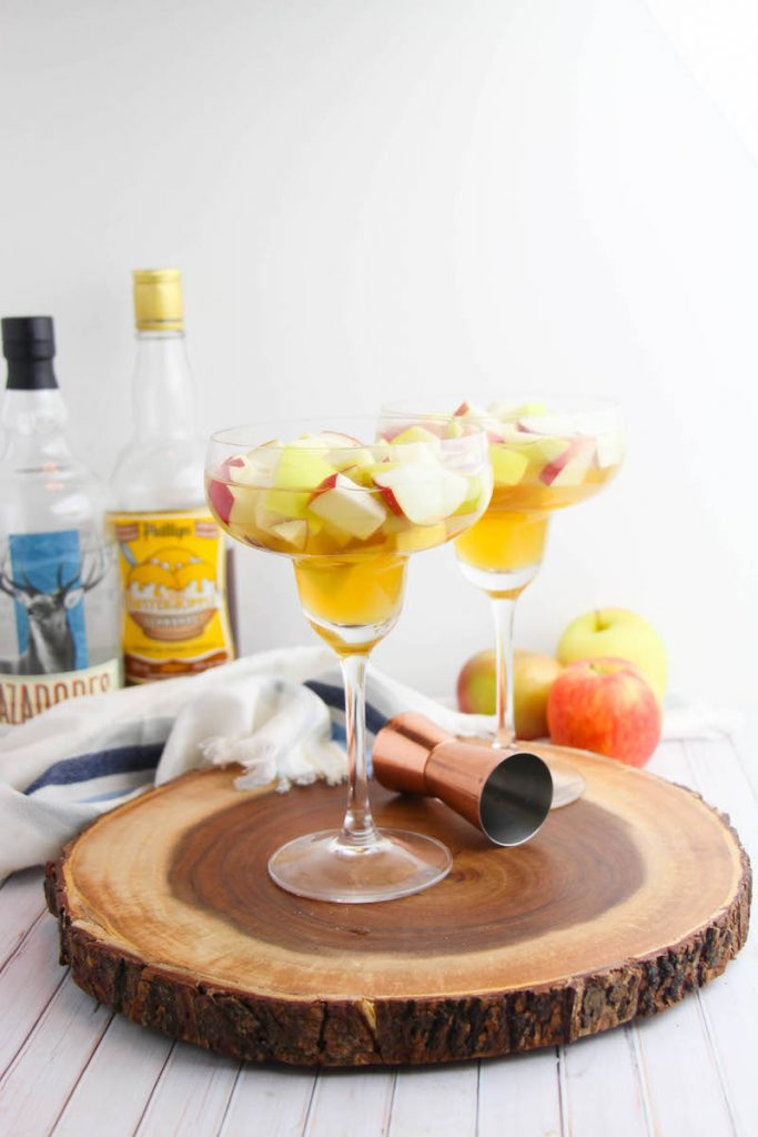 Apple Cider Margarita, two of them on the round wooden serving tray with ingredients show in the background as well.