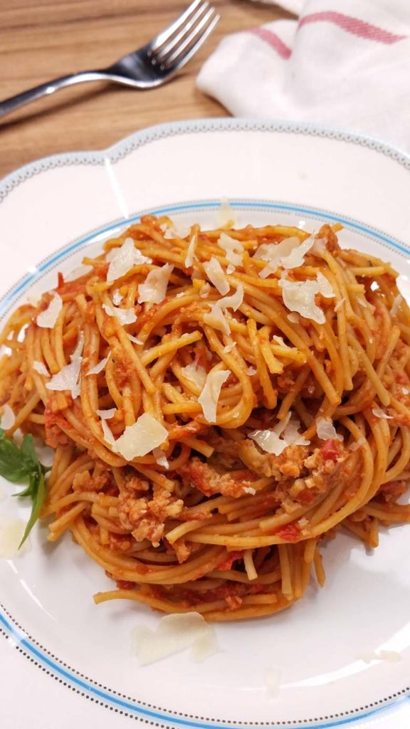 vertical image of spaghetti on a white plate