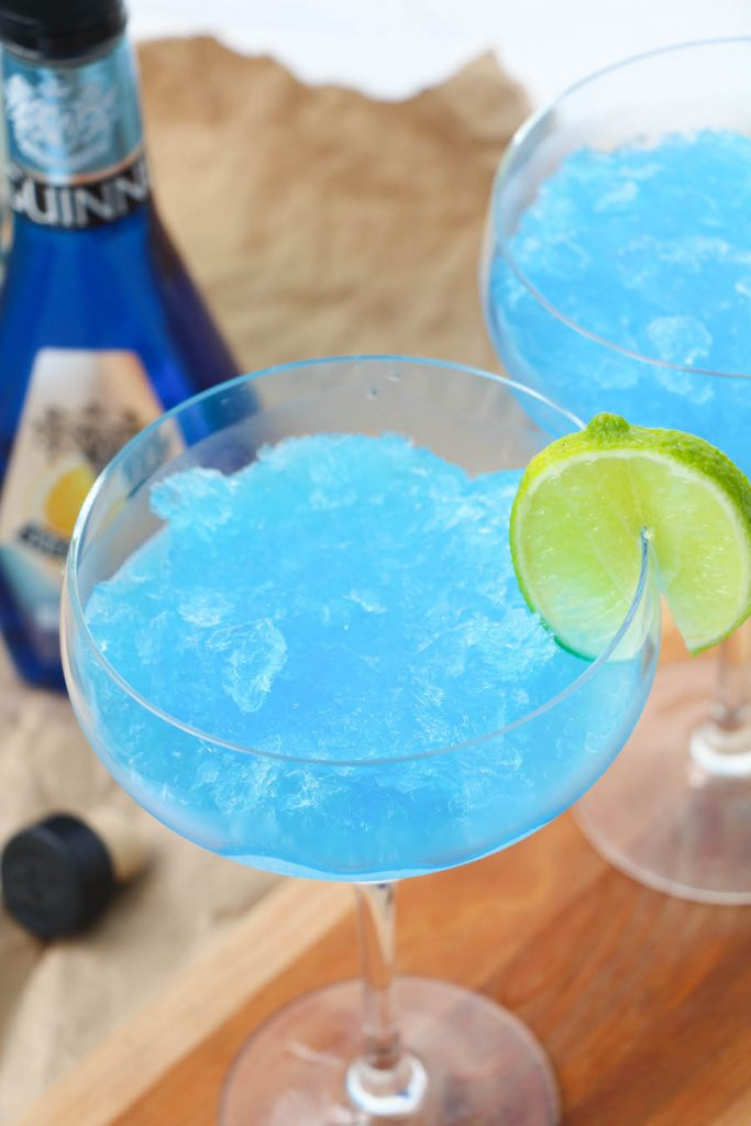 Top down shot of these frozen blue margaritas with a lime slice.