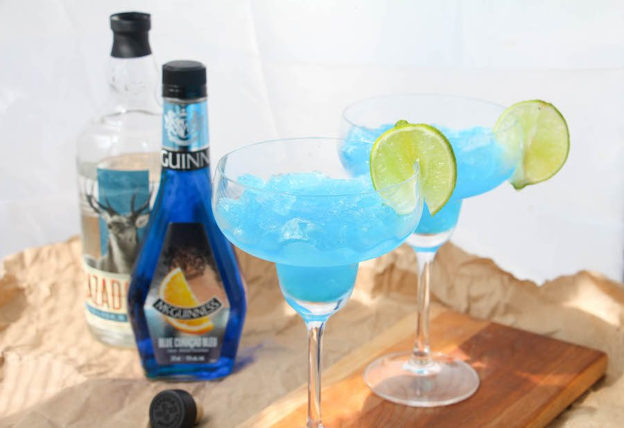 Two frozen blue margaritas on a wooden board with ingredients in the back.