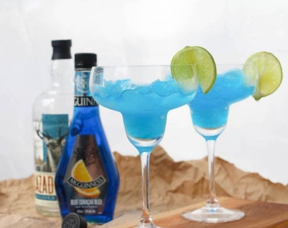 These frozen blue margaritas are delicious and simple! Give them a try today. This is a photo of the blue margarita mix frozen and placed in a glass with the ingredients in the background.