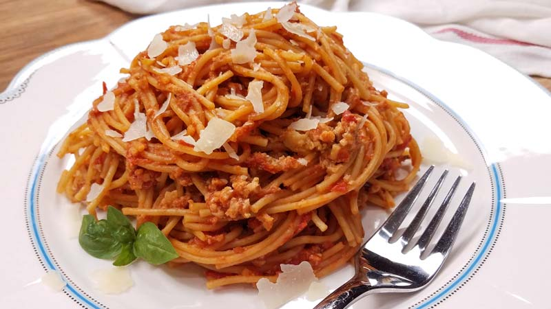 spaghetti with meat sauce on white plate with fork