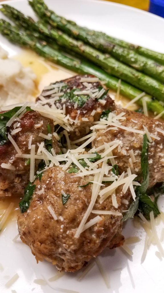 vertical image of meatballs with parmesean cheese on white plate