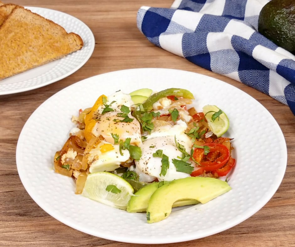 white plate with eggs and veggies, toast in background