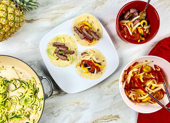 Finished steak fajitas on tortillas with zoodles.