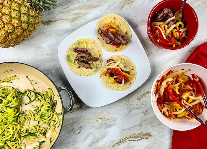Steak fajitas with zoodles on tortillas.