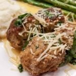 swedish meatballs with asparagus on a white plate