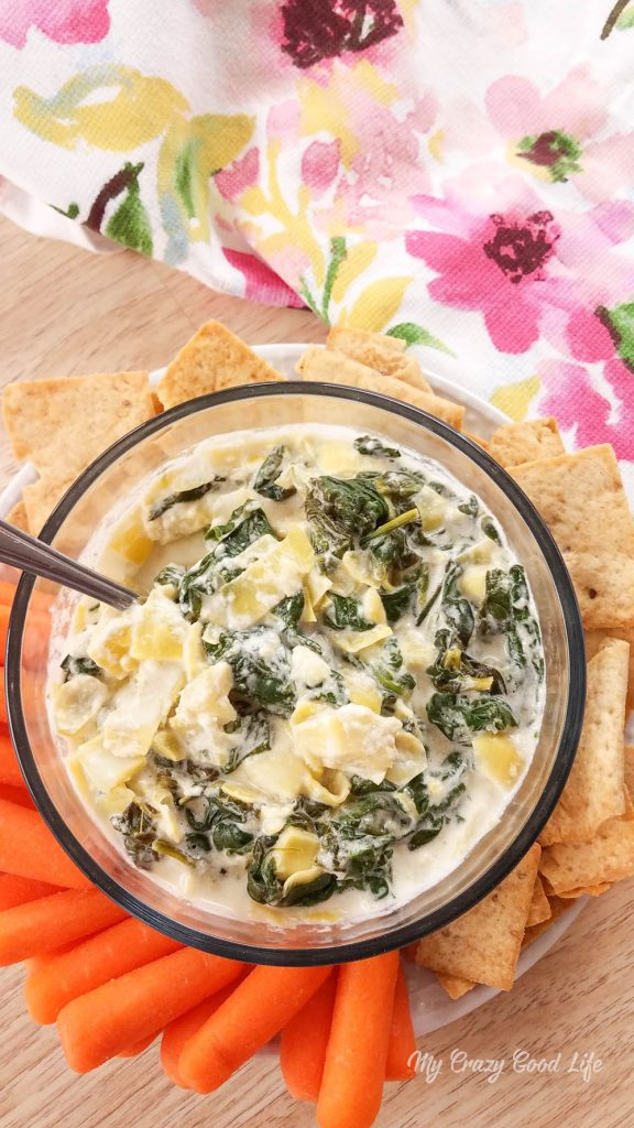 Healthy spinach artichoke dip on a platter surrounded by veggies and chips for dipping.