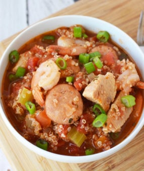 jambalaya in a white bowl on a wood table