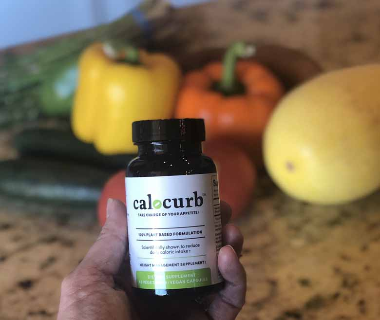 bottle of calocurb in front of healthy food