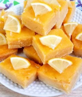 close up of cut lemon bars on a white plate
