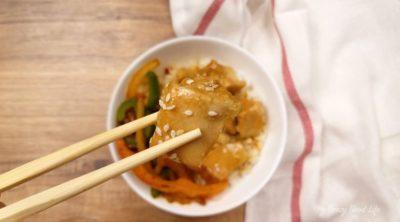 one bite of orange chicken in chopsticks