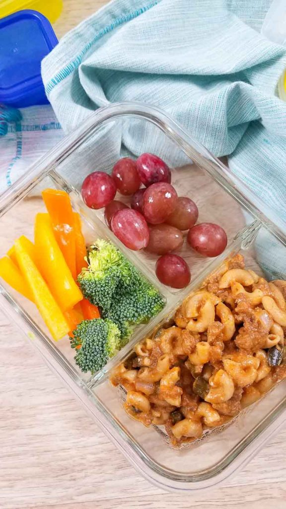 glass meal prep container with veggies, fruit, and hamburger helper