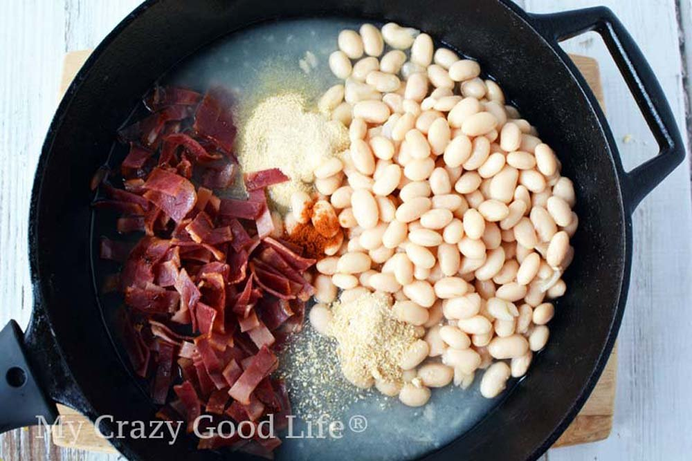 homemade pork and beans ingredients in a cast iron skillet