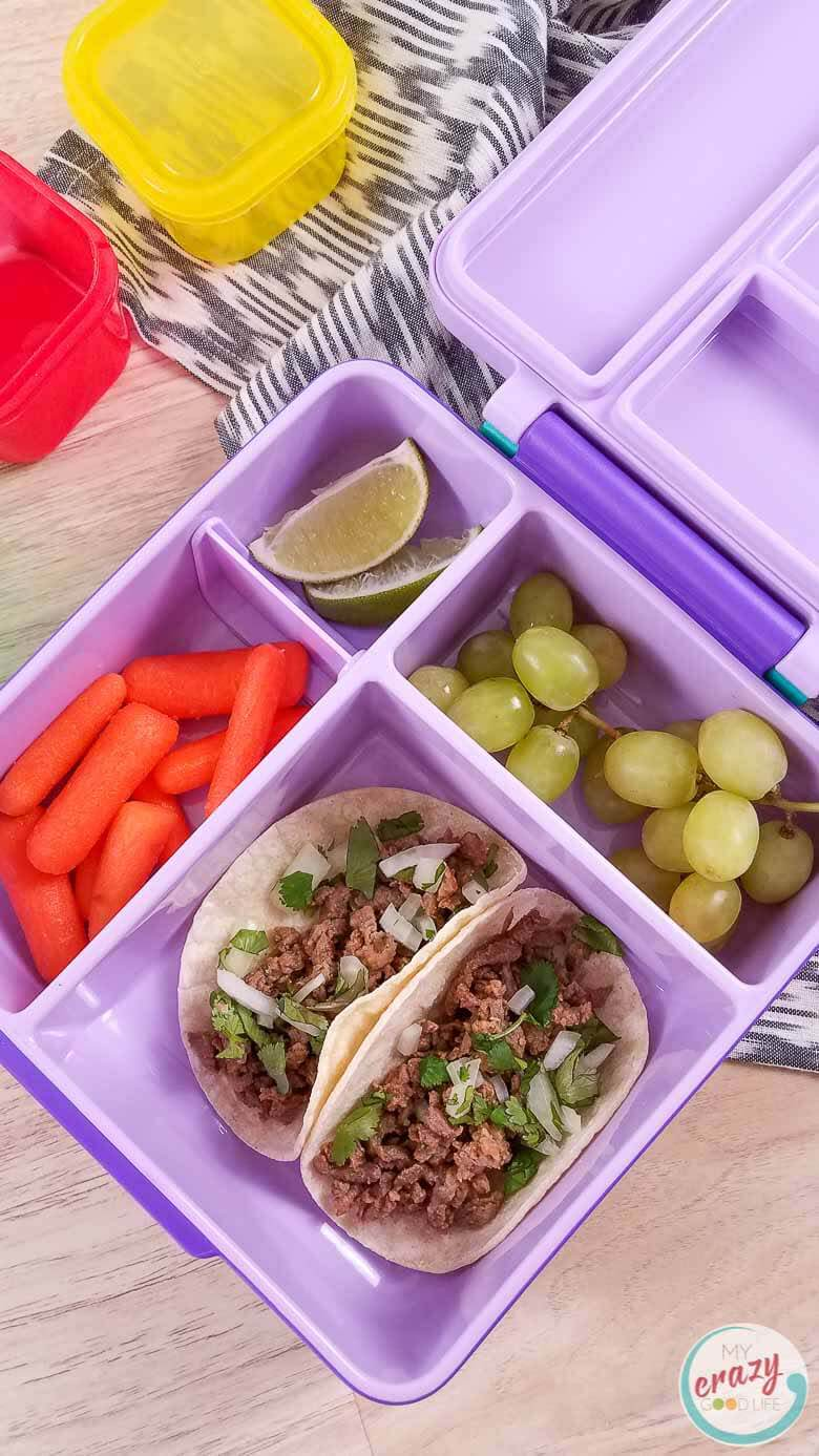 image of carne asada street tacos in a lunch bento box with fruit and vegetables