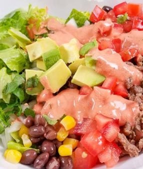 This Carne Asada Burrito Bowl includes a recipe for Homemade Creamy Chili Lime Dressing that's going to be your next favorite healthy dressing recipe! Citrus-seasoned Carne Asada and delicious vegetables and black beans make a delicious Mexican dinner for your Carne Asada leftovers!