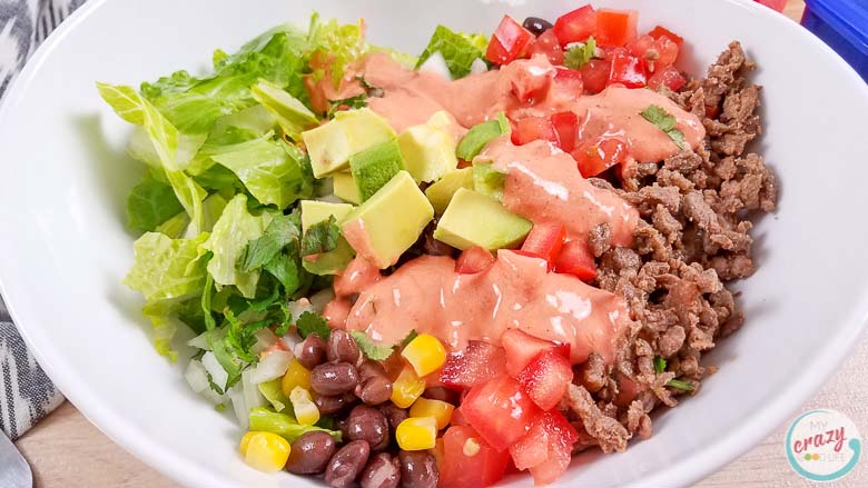burrito bowl with dressing in a white bowl