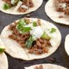 carne asada tacos on a black platter