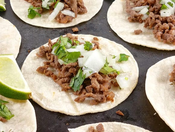 carne asada tacos on a black platter