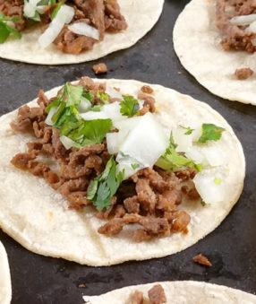 carne asada street tacos on a black platter