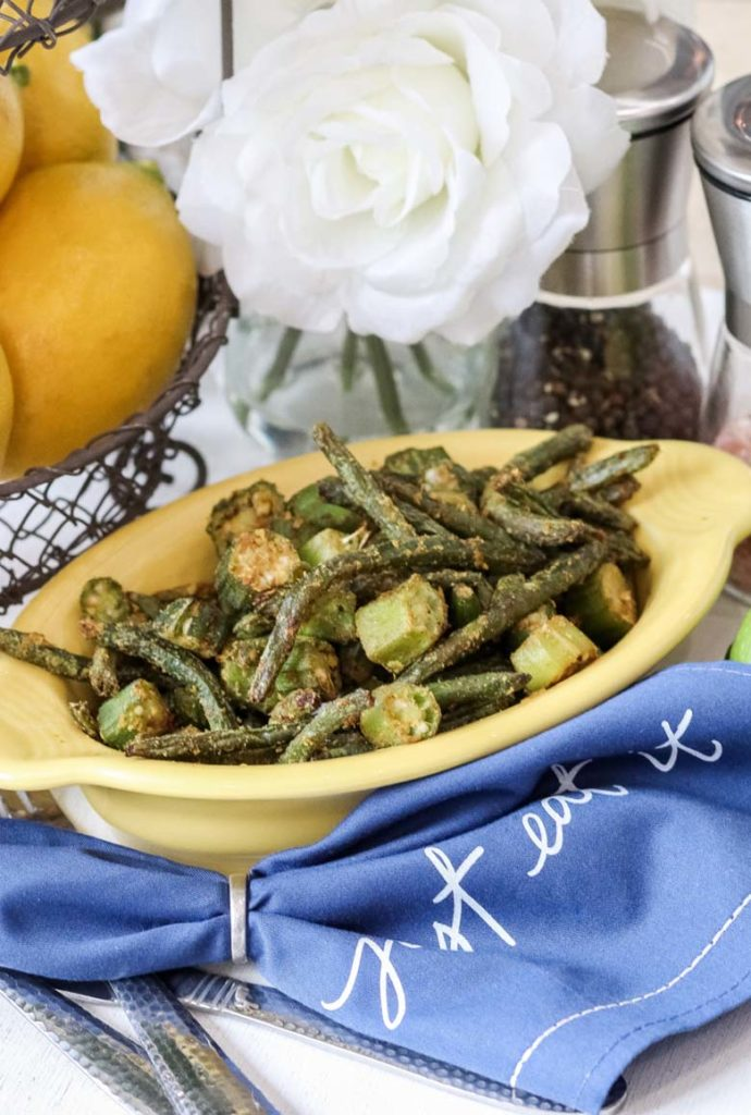 air fryer okra and green beans in a yellow bowl on top of a blue napkin