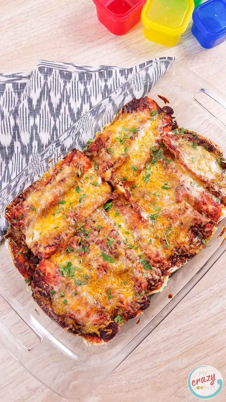 image of homemade beef enchiladas in a casserole dish on a gray and white towel