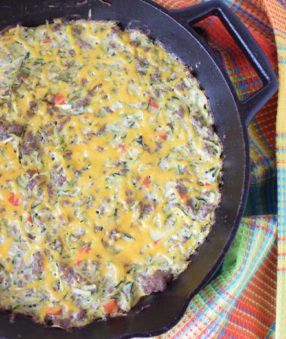 image of zucchini and sausage breakfast casserole in a skillet on a colored towel