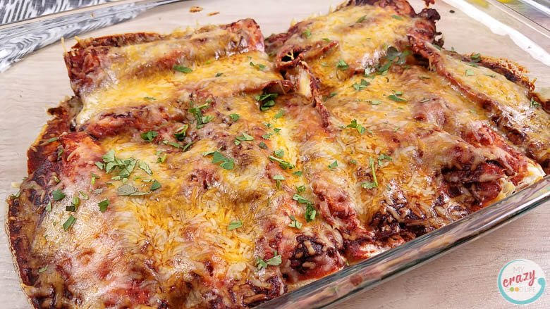 image of beef enchiladas right out of the oven in a clear casserole dish