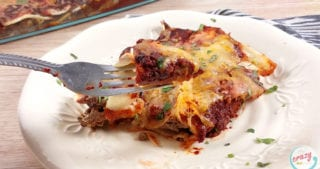 a white plate with healthy enchiladas-fork full of food