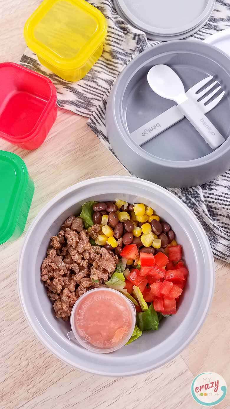 carne asada burrito bowl in meal prep container on wood counter