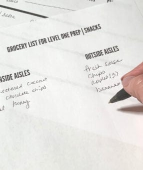 image of woman writing on a grocery list