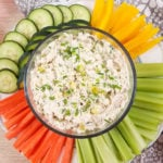 image of dill pickle chicken dip in a clear glass bowl with colorful dipping veggies