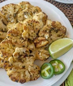 cauliflower steaks with lime and jalapeno on a white plate